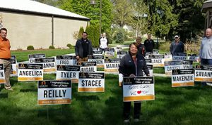 Athletic Director Janet Eaton and Lourdes University Coaches standing with yard signs congratulating graduates