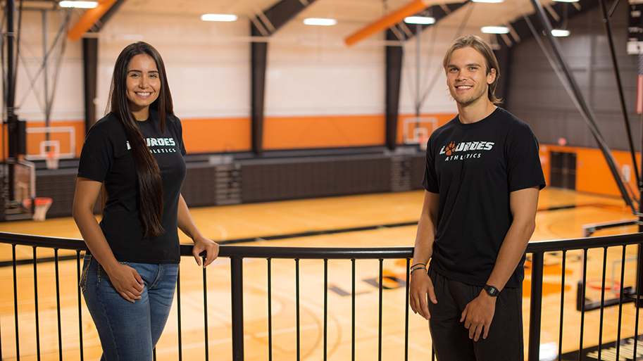 Photo of two Lourdes international students near the railing on the balcony in the Russell Ebeid Rec Hall. The Gray Wolves volleyball and basketball court is in the background