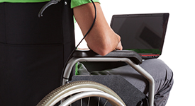 Image of individual with laptop in a wheelchair
