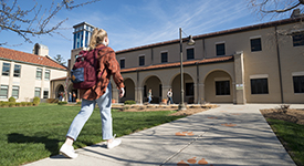 Image of student walking into Lourdes building