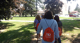 Image of students walking on campus grounds with a TRiO backpack