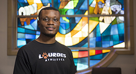 Photo of Lourdes University international student in front of stained glass background in a University building