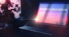 Image of a laptop opened with a web page that reads Business Education