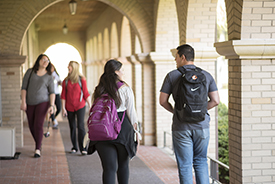 Students walking on campus under covered walkways