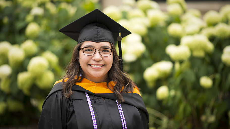 Image of Lourdes University graduate in front of flowers on campus
