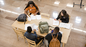 Photo of students around table doing school work