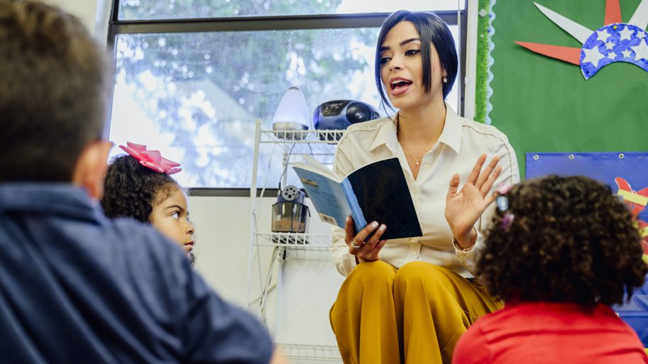 Schoolteacher Reading Aloud To Her Young Students