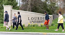 Students walking on Lourdes University campus grounds at entrance