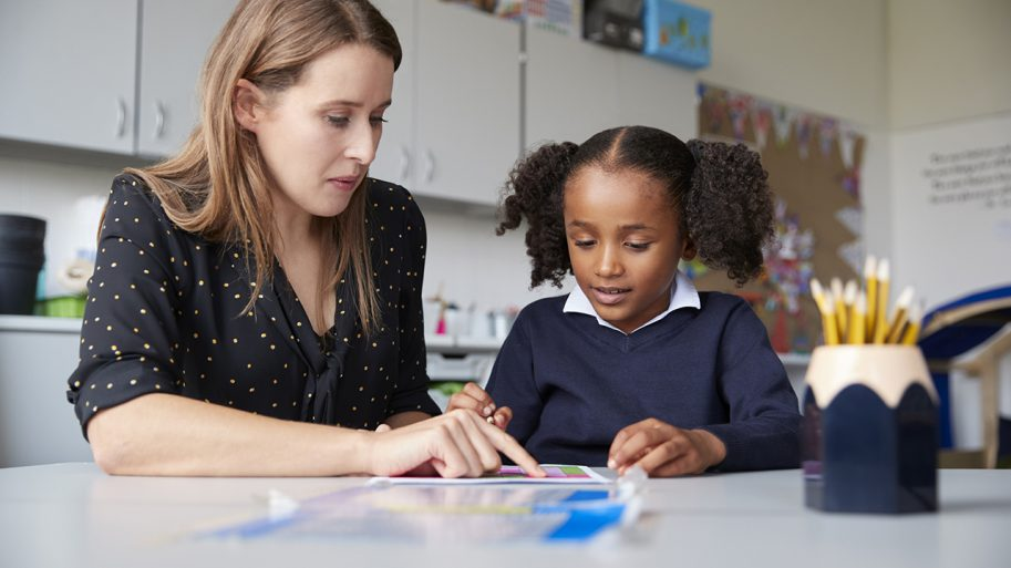 Young female primary school teacher working one on one with a schoolgirl at a table in a classroom, close up