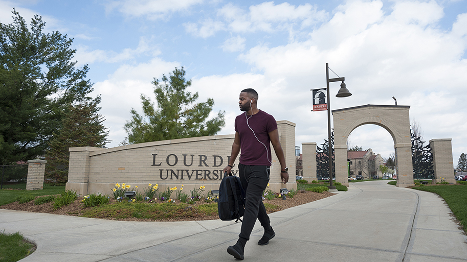Photo of Lourdes student walking on campus carrying a brief case or professional bag