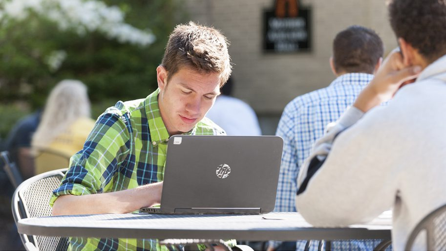 Student seated with laptop