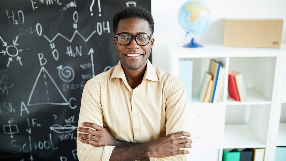 Teacher in front of chalk board in classroom