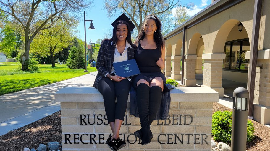 Two May 2021 Grads Seated Atop The Russell Ebeid Rec Center Sign Smiling After Graduating