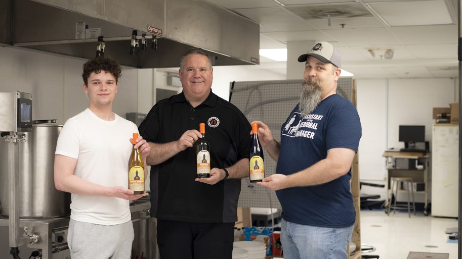 Craft Beverages faculty member with two students holding Lourdes University bottled wine