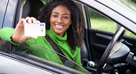 Happy female holding her drivers license as she sits in her car with the window open