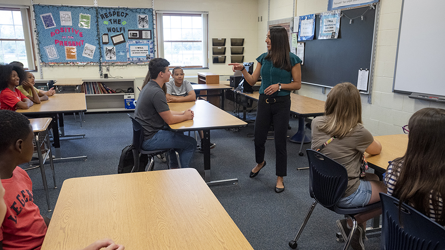 Photo of Educator Working With Middle Schoolers In Classroom